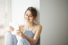 Portrait of young teenage cheerful girl in headphones smiling looking at tablet surfing web browsing internet sitting Royalty Free Stock Photography
