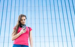 Portrait of young teenager brunette girl in coral t-shirt with long hair. girl on city looking on the smart phone. Glass building. Outdoor portrait of young stock photos