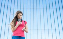 Portrait of young teenager brunette girl in coral t-shirt with long hair. girl on city looking on the smart phone. Glass building. Outdoor portrait of young stock photo