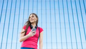 Portrait of young teenager brunette girl in coral t-shirt with long hair. girl on city looking on the smart phone. Glass building. Outdoor portrait of young royalty free stock images