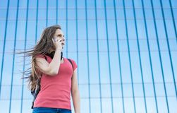 Portrait of young teenager brunette girl in coral t-shirt with long hair. girl on city talking on the smart phone. Glass building. Outdoor portrait of young royalty free stock photo