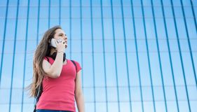 Portrait of young teenager brunette girl in coral t-shirt with long hair. girl on city talking on the smart phone. Glass building. Outdoor portrait of young stock images