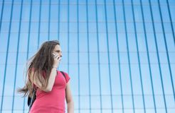 Portrait of young teenager brunette girl in coral t-shirt with long hair. girl on city talking on the smart phone. Glass building. Outdoor portrait of young stock image