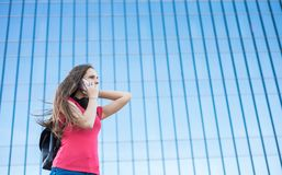 Portrait of young teenager brunette girl in coral t-shirt with long hair. girl on city talking on the smart phone. Glass building. Outdoor portrait of young stock photography