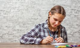 Young teenager brunette girl with long hair drawing with brush at a table on gray wall background with copy space. stock images