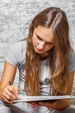 Young teenager brunette girl with long hair drawing with pencil on gray wall background royalty free stock image