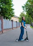 Portrait of young teenager brunette girl with long hair driving scooter on city street stock photography