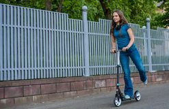 Portrait of young teenager brunette girl with long hair driving scooter on city street royalty free stock images