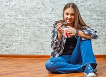 Portrait of young teenager brunette girl with long hair eating ice cream sitting on floor stock images