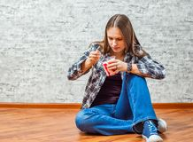 Portrait of young teenager brunette girl with long hair eating ice cream sitting on floor royalty free stock image