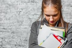 Young teenager brunette girl with long hair holding books and note books wearing backpack on gray wall background royalty free stock images