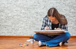 Portrait of young teenager brunette girl with long hair sitting on floor and drawing picture on gray wall background royalty free stock images