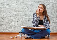 Portrait of young teenager brunette girl with long hair sitting on floor and drawing picture on gray wall background royalty free stock photography