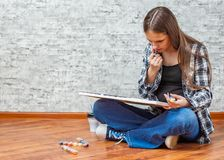 Portrait of young teenager brunette girl with long hair sitting on floor and drawing picture on gray wall background stock images