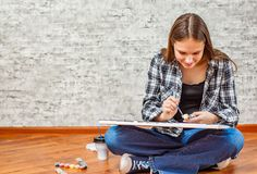 Portrait of young teenager brunette girl with long hair sitting on floor and drawing picture on gray wall background royalty free stock photos