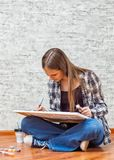 Portrait of young teenager brunette girl with long hair sitting on floor and drawing picture on gray wall background stock photography