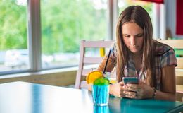 Young teenager brunette girl with long hair sitting indoor in urban cafe, drink a blue lemonade cocktail and use her smartphone royalty free stock images