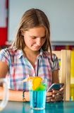 Young teenager brunette girl with long hair sitting indoor in urban cafe, drink a blue lemonade cocktail and use her smartphone royalty free stock image