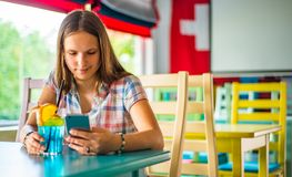 Young teenager brunette girl with long hair sitting indoor in urban cafe, drink a blue lemonade cocktail and use her smartphone royalty free stock photos