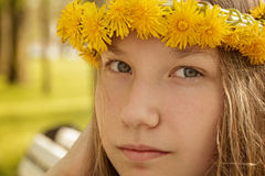 Portrait of young teenager girl on bench with wreath of dandelions. Summer time Stock Images