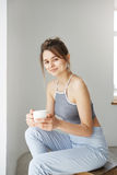 Portrait of young tender girl smiling holding cup looking at camera sitting on chair over white wall early in morning. Copy space Royalty Free Stock Images
