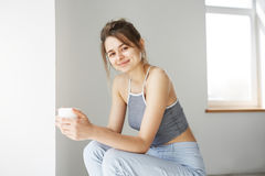 Portrait of young tender girl smiling holding cup looking at camera sitting on chair over white wall early in morning. Copy space Stock Photo