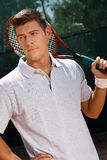 Portrait of young tennis player. Portrait of young male tennis player holding tennis racket, looking away Stock Image