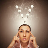 Portrait of the young  thinking woman looks up. Stock Photo
