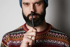Portrait of Young thoughtful bearded man in blue beanie thinking about test over empty background. Portrait of Young thoughtful bearded man in blue beanie royalty free stock photography