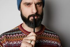 Portrait of Young thoughtful bearded man in blue beanie thinking about test over empty background. Portrait of Young thoughtful bearded man in blue beanie stock image