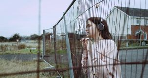 Portrait of young thoughtful girl dressed in pink vest with headphones. Pretty girl listening music , dreaming and stock footage