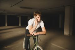 Young thoughtful man sitting on bicycle and talking on his cellphone. Cool boy with brown hair in white t-shirt leaning. Portrait of young thoughtful man sitting Stock Photo