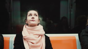 Portrait of young and thoughtful woman sitting in subway. Girl uses public transport, looking around, at window. Portrait of young and thoughtful woman sitting stock footage
