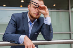 Portrait of young tired businessman with beard standing in front Stock Photos