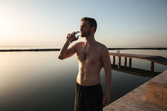Portrait of a young tired sportsman drinking water after jogging Stock Photos