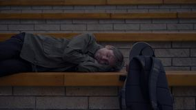 Portrait of young tired tourists lying on the bench with bags on street man sleep stock footage