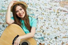 Portrait of young toothy smiling woman with guitar. Against brick grunge wall Stock Image