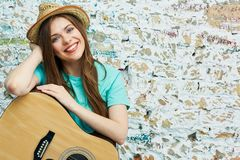 Portrait of young toothy smiling woman with guitar. Against brick grunge wall Royalty Free Stock Photography