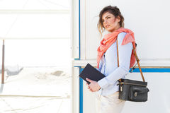 Portrait of young tourist woman holding a book and camera bag Stock Photo