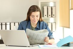 Young trainee reading a newspaper at office. Portrait of a young trainee reading a newspaper at office Royalty Free Stock Images