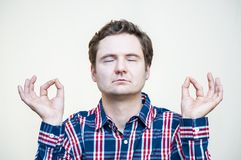 Meditating man with raised palms. Portrait of young tranquil meditating man on white background Royalty Free Stock Image