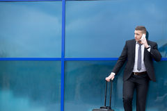 Portrait of young traveler in suit standing with suitcase and ma Royalty Free Stock Photos