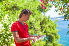 Portrait of young traveling man with map while Stock Photo