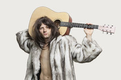 Portrait of young trendy man with guitar over gray background Royalty Free Stock Photo