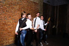 Portrait of young trendy musicians over a brick wall Royalty Free Stock Image