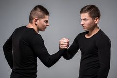 Portrait of young twin brothers standing face to face on gray ba. Ckground. Copy space. Casual twin brothers royalty free stock photo