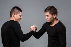 Portrait of young twin brothers standing face to face on gray ba. Ckground. Copy space. Casual twin brothers royalty free stock photography