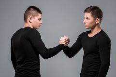 Portrait of young twin brothers standing face to face on gray ba. Ckground. Copy space. Casual twin brothers stock images