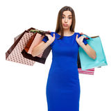 Portrait of young unhappy woman with shopping bags. Isolated over white background Stock Images