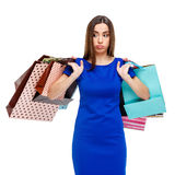 Portrait of young unhappy woman with shopping bags. Isolated over white background Royalty Free Stock Images